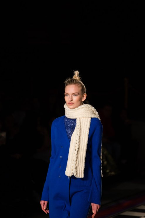 a model on the Apu Jan FW18 runway at London Fashion Week wearing a blue jacket and thick cream scarf