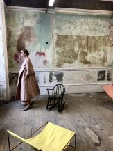 Merchant Archive FW18 LFW a model gazing out of the window in a pale pink wide hem dress coat