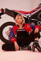 Honda & Forever 21 have teamed up for a race wear inspired collection featuring race jackets, motocross style pants etc. This standalone shot features a female model wearing a race jacket, bodysuit and black pants in front of a motorbike