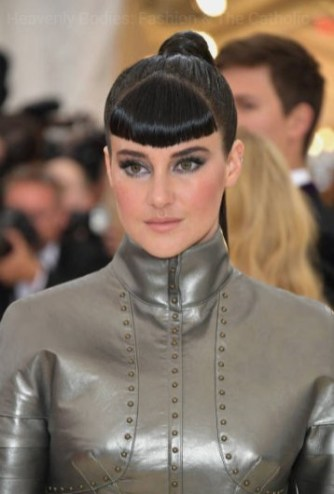 Shailene Woodley makes a nod to Joan of Arc on the red carpet at the 2018 met gala in a silver armoured tunic, stark beauty look, long black pony tail and thick set bangs