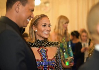 Jennifer lopez on the steps to the met gala wearing a bejewelled split front dress emblazoned with cross detailing posing with A-Rod