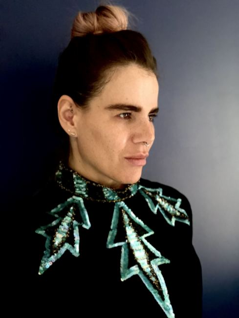 An image of Blogger Pixie tenenbaum wearing a floor length vintage gown with green sequin detailing, side view