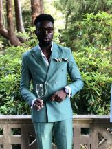 Menswear Tailor Duke Ata of Duke Ata Bespoke wearing a green suit with pocket square holding a glass of champagne as he gives a talk on his brand at the Slaley Hall Summer Soiree in Northumberland - Fashion Voyeur Blog