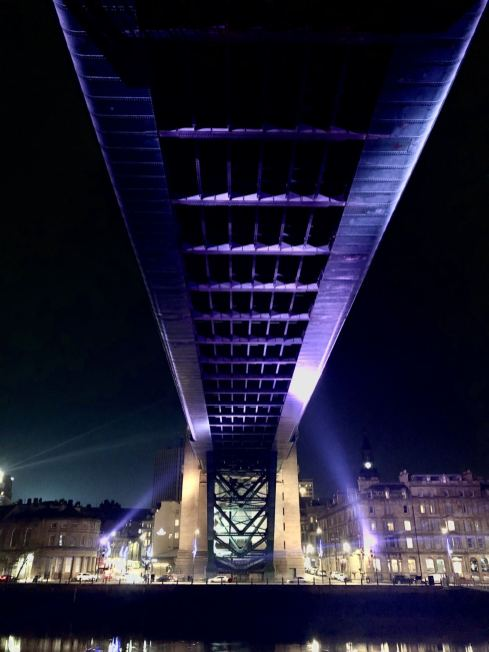 An image of the underside of the Tyne Bridge stretching from the Gateshead Quayside to the Newcastle Quayside lit up purple against the night sky. Image taken by Pixie Tenenbaum