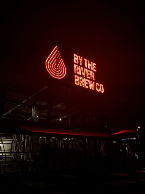 a night time image taken of the By The River Brew Company logo on the Gateshead Quayside