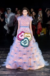 "a model in the Viktor & Rolf Spring 2019 Couture runway show in Paris featuring lots of tulle dresses bearing slogans, this one says ""Go Fuck Yourself"" in Love Hearts"