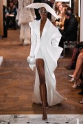 An image of a model on the runway for Balmain at the Spring 2019 couture show in Paris wearing an open fronted white dress and a huge bangle