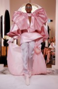 An image of a runway model at the Balmain couture Spring 2019 show wearing a huge pink satin outfit and thigh high boots