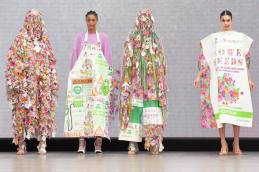 A group of models on the runway for the Liverpool John Moores University Graduate Fashion Week 2019 runway show wearing clothes which look like flower seed packets