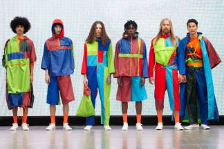 A group of models on the runway for the Liverpool John Moores University Graduate Fashion Week 2019 runway show wearing shellsuit style pieces in multiple colours