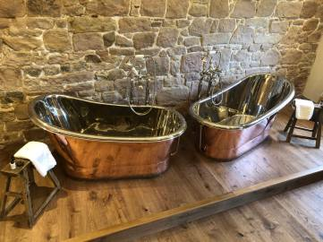Inside the Muckle Hoose suite at Beadnell Towers Hotel with it's copper bathtubs on a backlit plinth