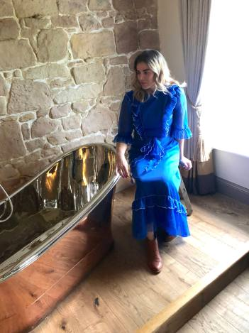 Pixie Tenenbaum sits on a milking stool next to a copper slipper tub at Beanell Towers Hotel in Northumberland | Fashion Voyeur Blog