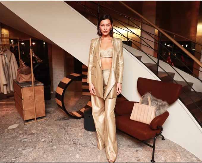 Bella Hadid, wearing Max Mara gold blazer, gold trousers, gold bralette and tan Whitney bag design by Renzo Piano Building Workshop,