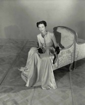 The Duchess of Windsor, sitting in an armchair and wearing a cap-sleeved, silk shantung gown by Mainbocher with black satin gloves and a gold necklace with sapphires and rubies *** Local Caption *** Duchess of Windsor;