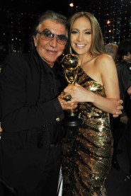 Roberto Cavalli with Jennifer Lopez who was wearing a spectacular vintage gown from the Roberto Cavalli FW 2004 – 2005 collection. It is completely embroidered with gold sequins and has a feather train.