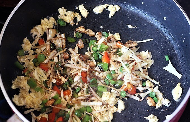 cooking vegetables, chicken and egg with sauces in a pan