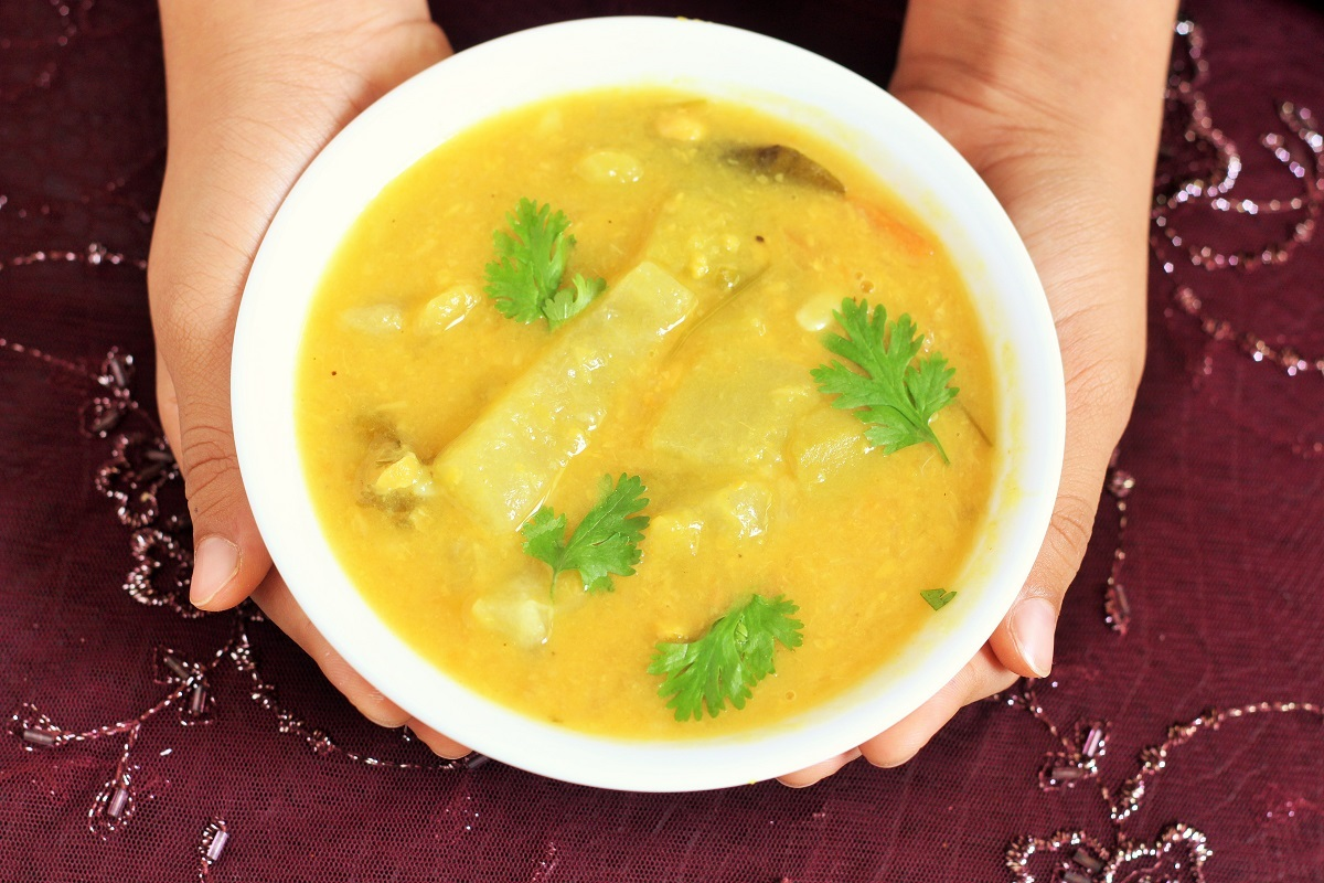 holding hyderabadi dalcha recipe in a white bowl