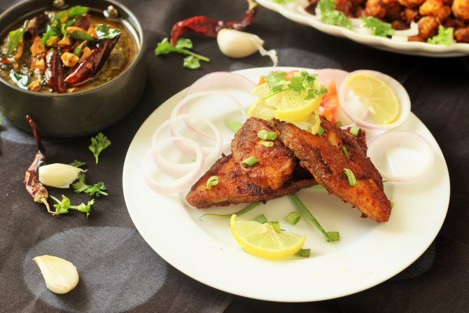 pomfret fish fry recipe in a white plate garnished with coriander leaves, lemon wedges