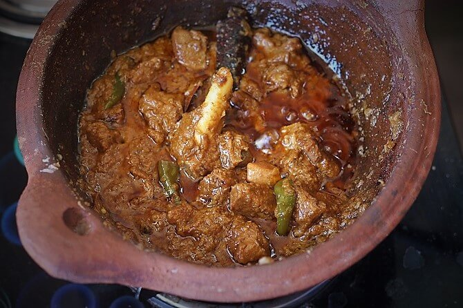 cooking mutton masala in a clay kadai