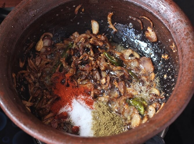 spices added to browned rice in clay pot