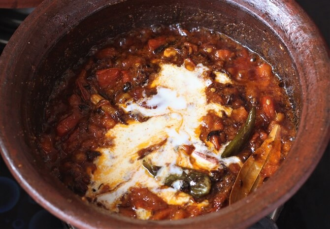 yogurt added to tomato masala for preparing hyderabadi egg biryani