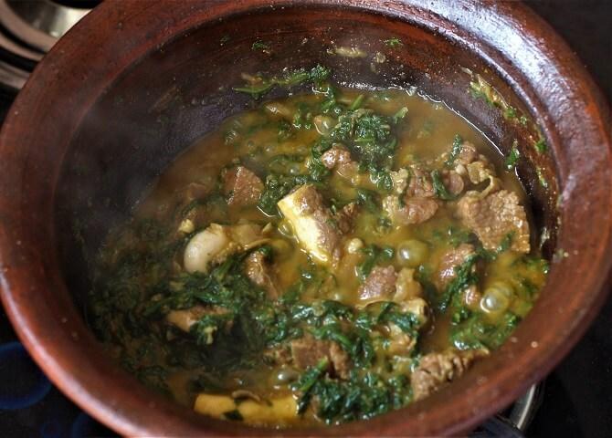 palak gosht recipe getting prepared in a clay pan