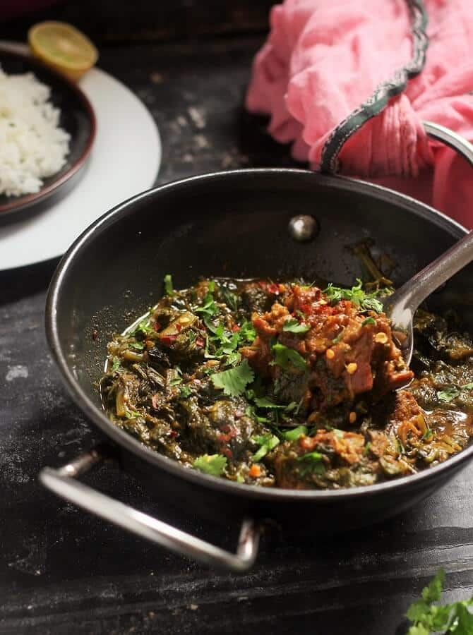 spinach mutton curry served in a kadai garnished with coriander leaves