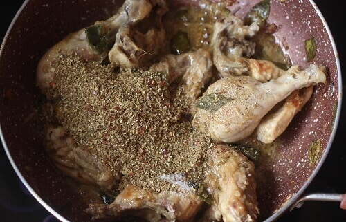 adding spice powder to the cooked chicken