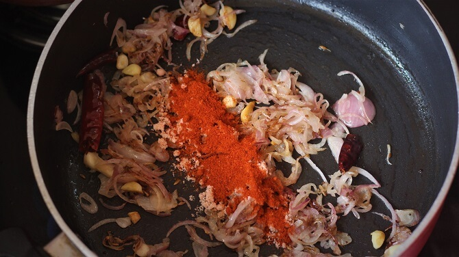 spices added to the cabbage stir fry in a black pan