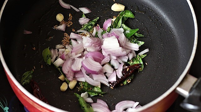 onion added to tempering in a black pan