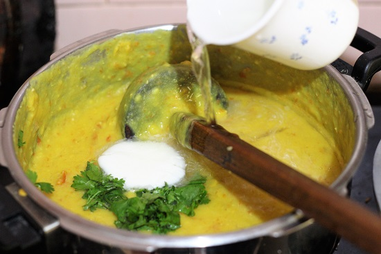 water, butter, coriander leaves added to mashed mix dal in a pressure cooker