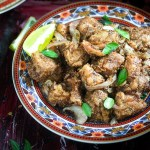 mutton varuval recipe in a plate with lemon wedges