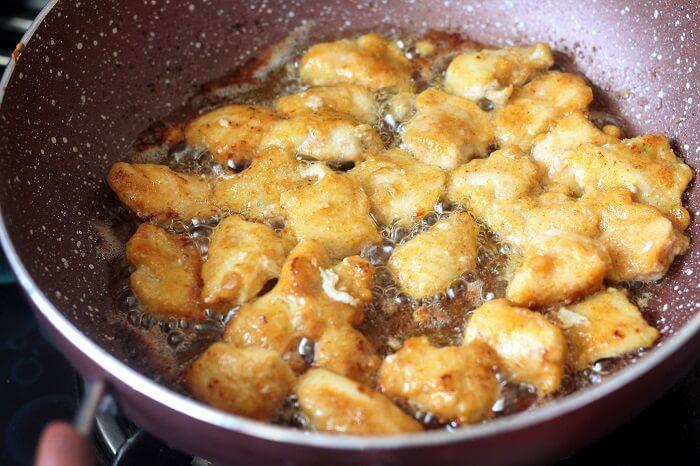 frying chicken in oil in a kadai