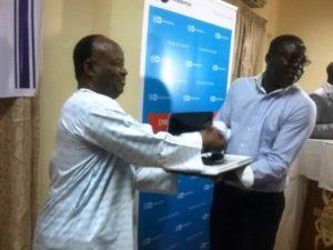 Le représentant du Ministre de la Communication, M. Adama Coulibaly (à gauche) remettant le 1er prix à Jean Carène Kaboré