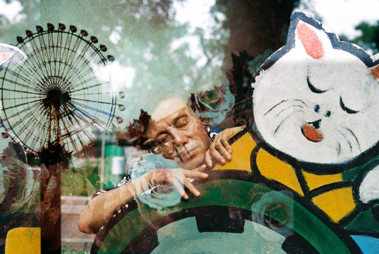 My father with the cat toys in Lenin Park, Hanoi, is overlaid by a pattern of ferris wheel from water park in Hanoi, Viet Nam on August, 2013.