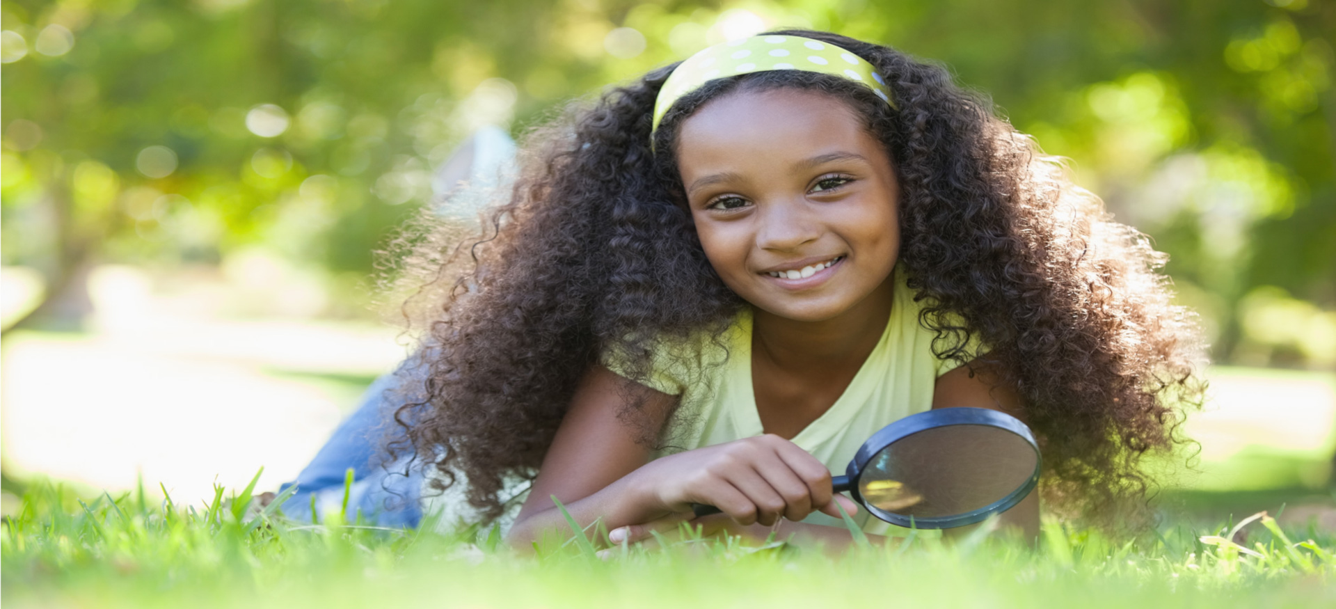 Image of a young girl on the grass with a magnifying glass