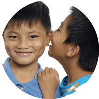 image showing one young boy speaking into the ear of another.