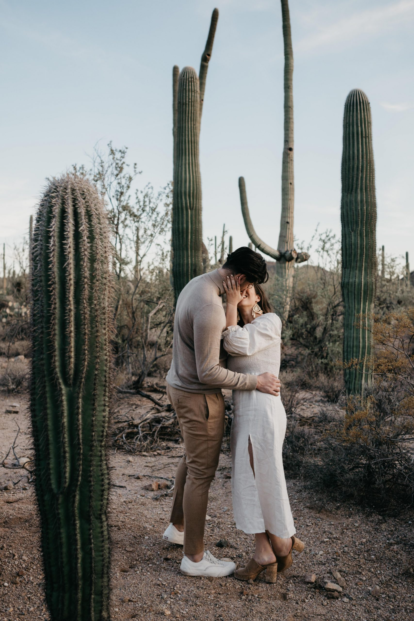 Couple kisses during their desert engagement photos, image by Fatima Elreda Photo