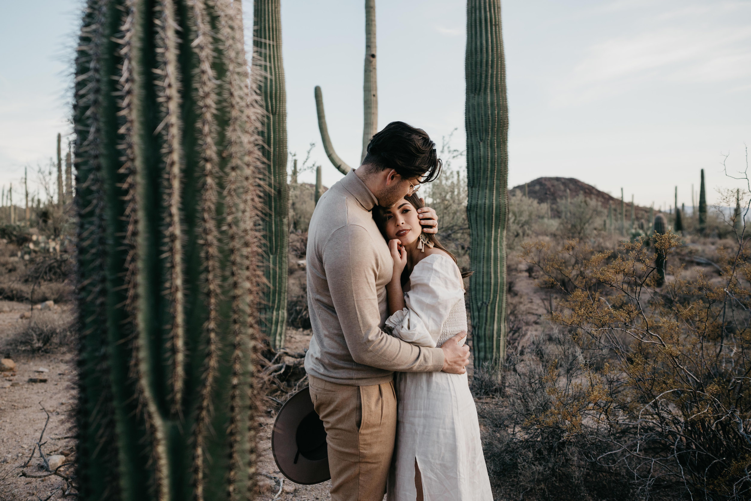 Couple embracing during their desert engagement photoshoot, image by Fatima Elreda Photo
