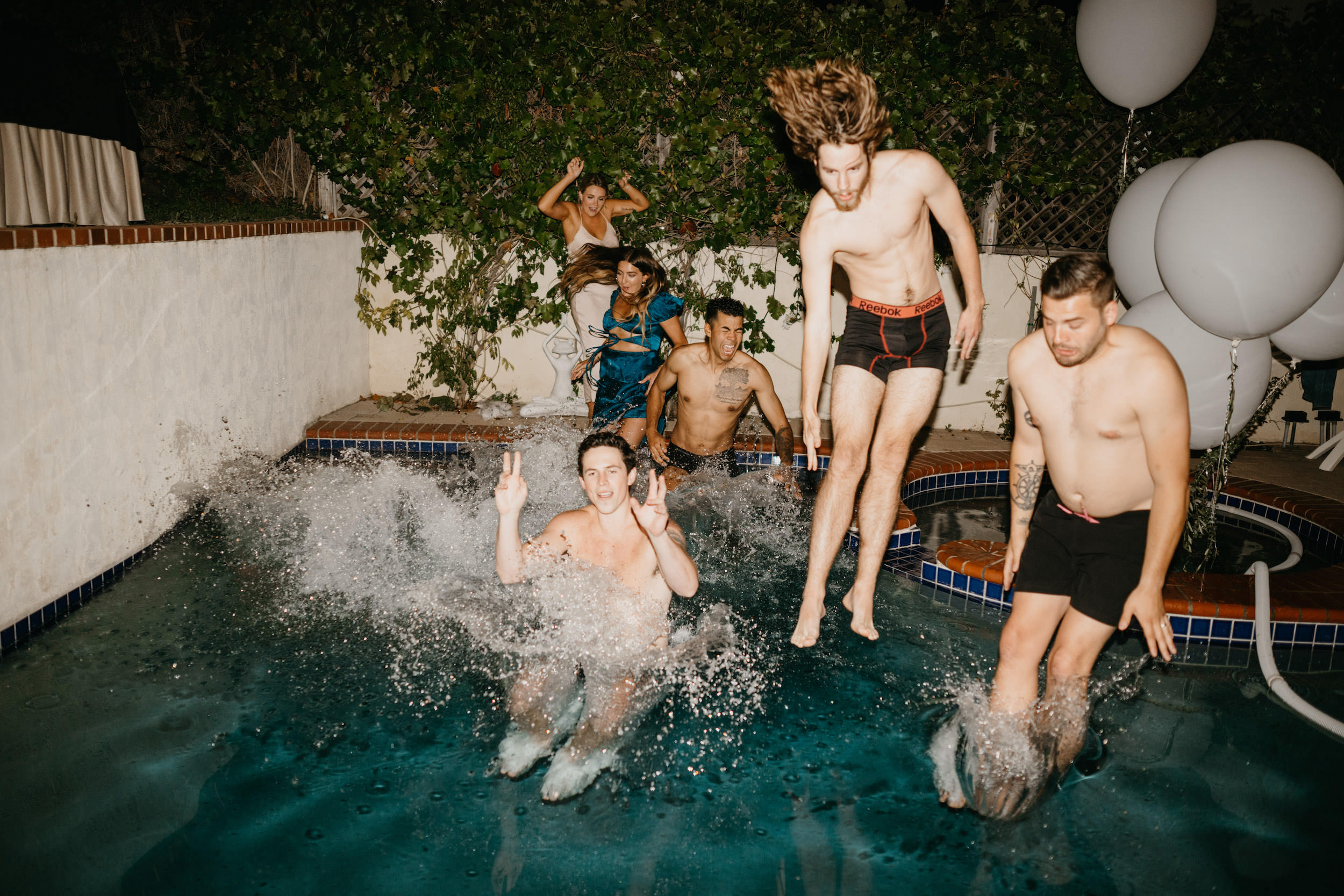 Bridal party jump into pool at the end of the wedding day in Laguna Beach Backyard Wedding, image by Fatima Elreda Photo