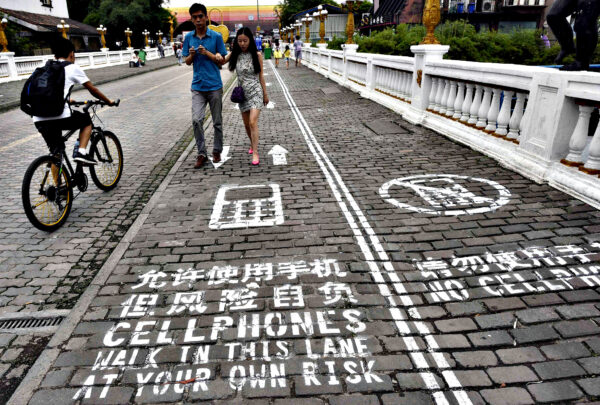 """A man rides his bicycle as people walk on the """"first mobile phone sidewalk in China"""", which was recently installed at a tourism area in Chongqing municipality...A man rides his bicycle as people walk on the """"first mobile phone sidewalk in China"""", which was recently installed at a tourism area in Chongqing municipality, September 13, 2014. The mobile phone sidewalk in Chongqing was divided into two sides -- one was written with """"Cellphones walk in this lane at your own risk"""" while the other with """"No cellphones"""", as an attempt to reduce pedestrian incidents, local media reported. Picture taken September 13, 2014. REUTERS/China Daily (CHINA - Tags: SOCIETY SCIENCE TECHNOLOGY) CHINA OUT. NO COMMERCIAL OR EDITORIAL SALES IN CHINA"""