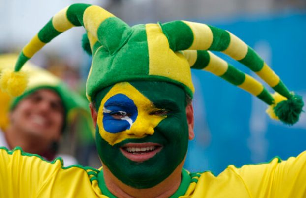 A Brazilian fan wears his nation's flag as face paint before the group A World Cup soccer match between Brazil and Mexico at the Arena Castelao in Fortaleza, Brazil, Tuesday, June 17, 2014. (AP Photo/Eduardo Verdugo)