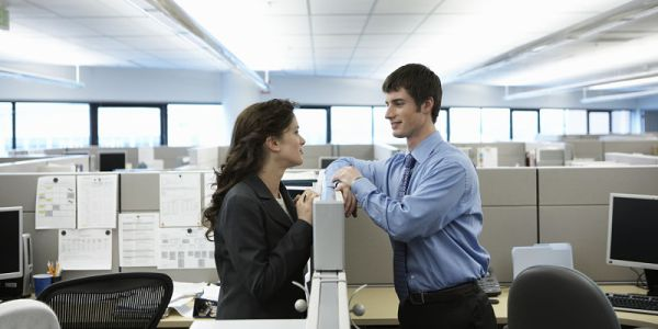 Two executives having conversation over cubicle wall, side view