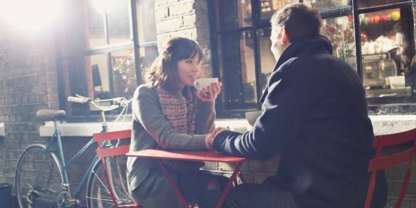 Couple having coffee at sidewalk cafe