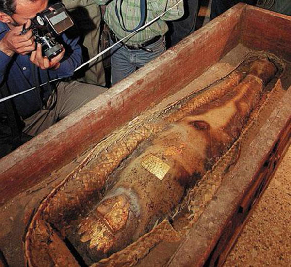"""Original Caption: Pakistani photographers hover over an ancient mummy show for the first time, during a press conference at the National Museum in Karachi, 26 October 2000. The mummified """"princess"""" in a gold-studded casket could have originated in Egypt or Iran before appearing on Pakistan's blackmarket.  AFP PHOTO/Aamir QURESHI"""