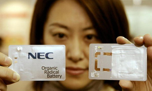 """TOKYO, JAPAN:  An employee of NEC shows off a card-size sample and its open model to use thier new ultra-thin, flexible, rechargeable """"Organic radical battery"""" (ORB) during the iExpo2005"""" exhibition in Tokyo, 09 December 2005. NEC says it has capable of super-fast (30-second) charging and can be embedded into smartcards and intelligent paper.The ORD uses a type of plastic called organic radical polymer as its cathode.    AFP PHOTO / TOSHIFUMI KITAMURA  (Photo credit should read TOSHIFUMI KITAMURA/AFP/Getty Images)"""