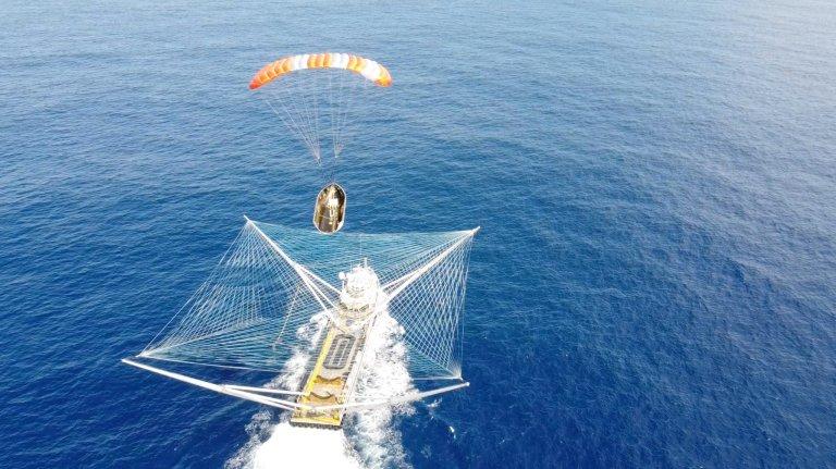 Veja um barco com uma rede gigante pegando peça de foguete caindo do céu