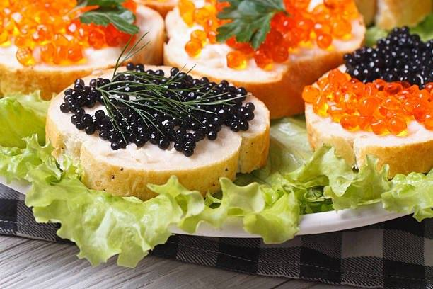 Sandwiches with red and black fish caviar on lettuce macro horizontal