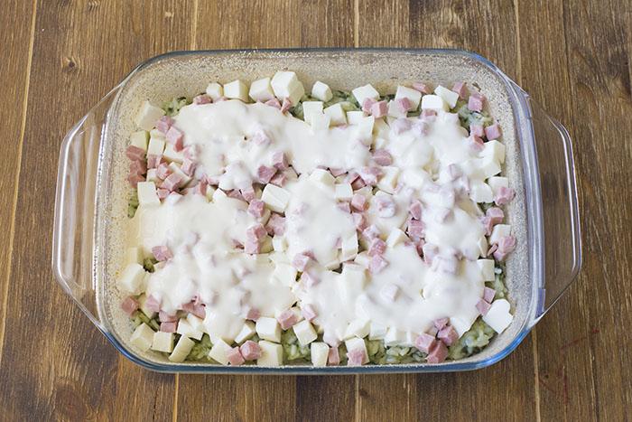 Trasferiamo metà del risotto in una teglia da forno precedentemente oliata e cosparsa di pangrattato. Livelliamo il riso con il retro di un cucchiaio, quindi farciamo con la mozzarella tagliata a dadini, i cubetti di prosciutto e qualche cucchiaiata di besciamella.