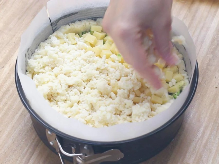 Adesso con l'impasto di patate avanzato ricopriamo il tutto, prendiamo dei pezzettini con le mani e li distribuiamo sulla superficie. In questo modo si creano dei ricciolini di patate che in cottura diventeranno croccanti. Terminiamo con una spolverata di formaggio grattugiato (10 gr circa).